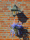 Lamp and Flower Pot on a Brick Wall. Of a Dutch House Stock Image
