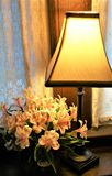 Lamp with flowers. A lamp shines yellow light onto flowers with pink and white petals against lace curtains and liwood wall Stock Image