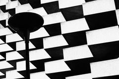 Lamp on foreground of geometric building Stock Images