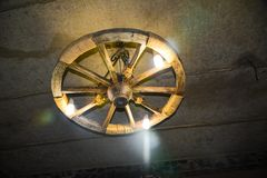Lamp in the form of a wheel under the ceiling in the wine storage royalty free stock photo