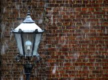 Lamp in front of a wall with snowing background stock images