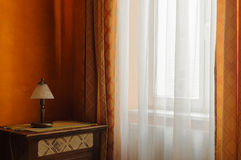 Lamp in front of the window in the room. The interior in orange tone with a lamp and curtains Stock Image