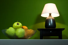 Lamp with fruits. Green room, lamp and fruits in bowl Royalty Free Stock Images
