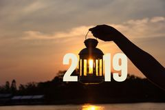 Lamp on hand in sunbeam over sunset with 2019 . power and idea concept. Lamp on hand in sunbeam over sunset with 2019. power and idea concept stock photography