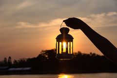 Lamp on hand in sunbeam over sunset. power and idea concept stock photos