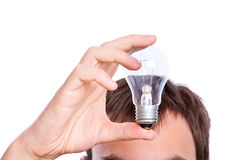 Lamp in hand under man's head Stock Image