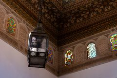 Lamp hanging from a decorated ceiling and walls with stained glass. Marrakech, Morocco royalty free stock image
