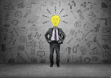 Lamp-headed businessman on background of concrete wall with business doodles Royalty Free Stock Photos