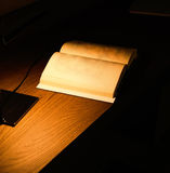 Lamp illuminating a book on wooden table Stock Image