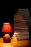 Lamp illuminating books Stock Photos