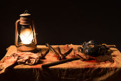 Lamp, knife and a mask on the table. On a gray background Royalty Free Stock Photos