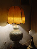 Lamp with the lamp shade about an old wall. Evening twilight Royalty Free Stock Photography