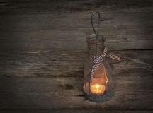 Lamp-lantern with a candle on wooden background Stock Images