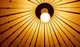 Lamp light bulb. Glowing lamp light bulb under bamboo lampshade Royalty Free Stock Photo