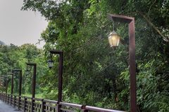 Lamp light poles and rays on the bridge, open one. Lantern that shines a light on the light poles at the bridge over the river with tree in the park, outdoor Royalty Free Stock Photo