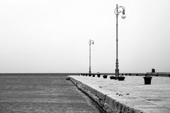 Lamp lights on pier by sea Royalty Free Stock Photos