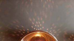 Lamp made from a colander. Soft shadows and lights. Abstract background. Light dots from a bulb light. Abstract background. Metallic and golden abstract stock image