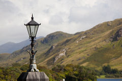 Lamp With Mountains In The Background. Lantern With Cloudy Sky And Mountains In The Background Stock Photos