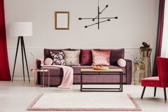 Sophisticated living room interior. Lamp next to a violet sofa with decorative cushions in sophisticated living room interior with mockup Stock Images