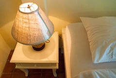 Lamp on a night table next to a bed royalty free stock photography