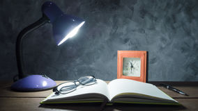 Lamp with notebook,pen,clock and glasses  on  wooden table with. Vintage wall background Stock Images