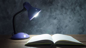 Lamp and notebook on the wooden table with vintage wall backgrou. Nd Stock Photo