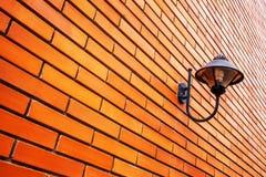 Lamp op oranje bakstenen muur stock afbeeldingen