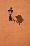 Lamp on Orange Wall. Street lamp casting a long shadow on an orange wall in the historic Spanish colonial city of Cartagena de Indias royalty free stock image