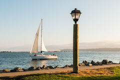 Lamp and Path with Sail Boat in San Diego Bay. Lamp on Harbor Island with sail boat in San Diego Bay and Point Loma in the distance Stock Photos