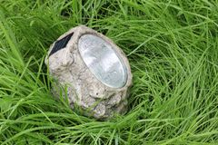 Lamp with photocell in the wet grass Royalty Free Stock Photo