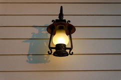 Lamp on the plank wall. Lamp is shining gently on the white wooden wall Stock Photo