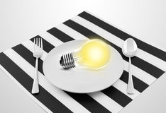 Lamp in plate and fork and spoon Royalty Free Stock Image