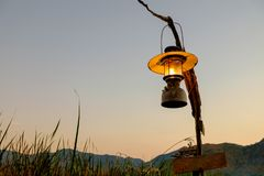 The lamp that is on the pole set the corridors to a lake or a river right in front of the mountain. In a morning sunrise or sunset Royalty Free Stock Images