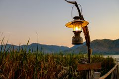 The lamp that is on the pole set the corridors to a lake or a river right in front of the mountain. In a morning sunrise or sunset Royalty Free Stock Photos