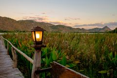The lamp that is on the pole set the corridors to a lake or a river right in front of the mountain. In a morning sunrise or sunset Stock Photography