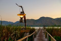 The lamp that is on the pole set the corridors to a lake or a river right in front of the mountain. In a morning sunrise or sunset Stock Photo