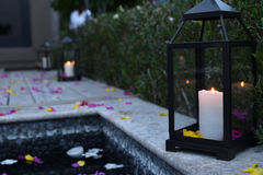 Lamp by pool with flowers. Candles in lamp next to pool with floating flower petals outdoors Stock Photography