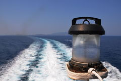 Lamp. Position lamp on the ferry from Skiathos to Skopelos, Skiathos island in the background Royalty Free Stock Images