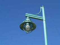Lamp on Post. A modern metal street lamp mounted on a post and framed against the blue sky Stock Images