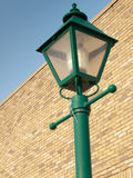 Lamp Post on brick. Top of a green lamp post, with a brick wall and blue sky in the background Royalty Free Stock Images