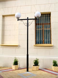 Lamp Post in Courtyard. A decorative lamp post with white globes stands next to the outside wall of a building on a brick courtyard Stock Image