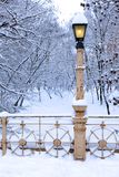Lamp post covered by snow in park Royalty Free Stock Photos