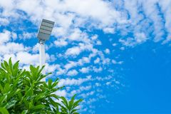 Lamp post electricity industry with blue sky background and tree. Spotlight tower against blue sky. street lamp. modern light pole royalty free stock photo