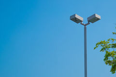 Lamp post electricity industry with blue sky background and tree Royalty Free Stock Image