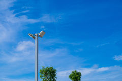 Lamp post electricity industry with blue sky background and tree. Spotlight tower against blue sky. street lamp. modern light pole Stock Photos