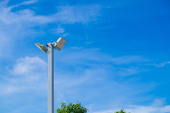Lamp post electricity industry with blue sky background and tree. Spotlight tower against blue sky. street lamp. modern light pole Royalty Free Stock Images