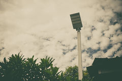 Lamp post electricity industry with blue sky background and tree. Spotlight tower against blue sky. street lamp. modern light pole, vintage tone Stock Images