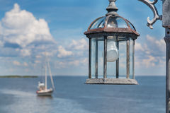 Lamp post with light bulb by the ocean Stock Photos