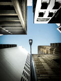 Lamp Post in Middle of Four High Rise Building Above Blue Sky during Daytime Royalty Free Stock Photography