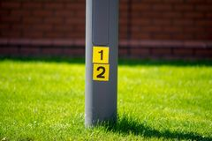 Post with numbers in yellow squares with green grass. Lamp post with 1 and 2 on it symobilising half measures or number twelve Royalty Free Stock Images